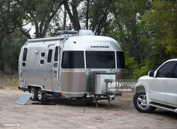 An Airstream Safari travel trailer with a solar panel kit parked in Ojo Caliente New Mexico