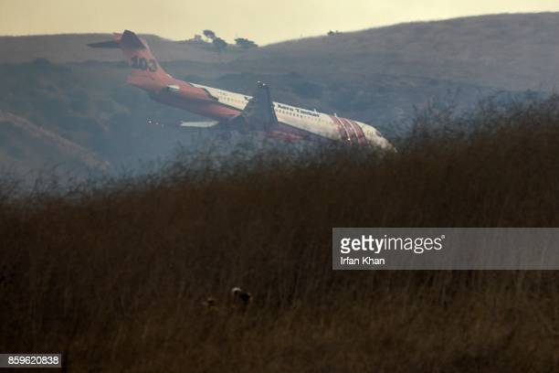 An airtanker dives behind the hills at Peters Canyon Regional Park to drop fire retardant on October 9 2017 in Orange California