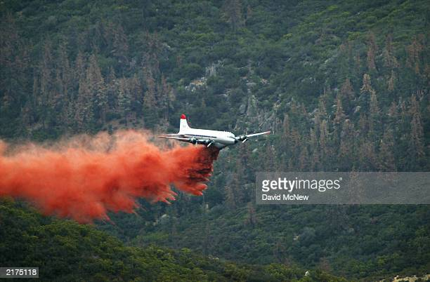 An airtanker drops fire retardant against a backdrop of dead trees killed by bark beetles as the Coyote Fire burns more than 13000 acres of chaparral...