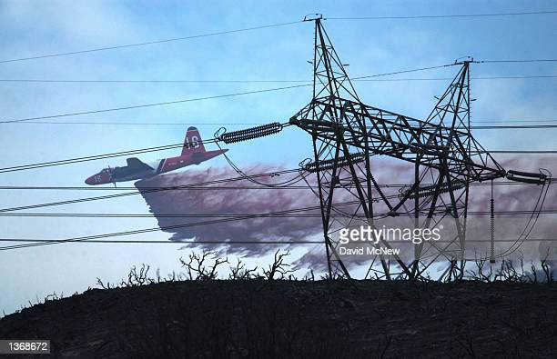 An airtanker drops fire retardant near high power lines on September 4 2002 in Leona Valley west of Palmdale California Heat from the wildfire caused...