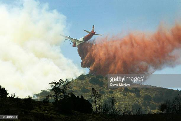 An airtanker drops fire retardant over Mount Emma Ridge at the Crown Fire on July 21 2004 south of Palmdale California The fire which began near...