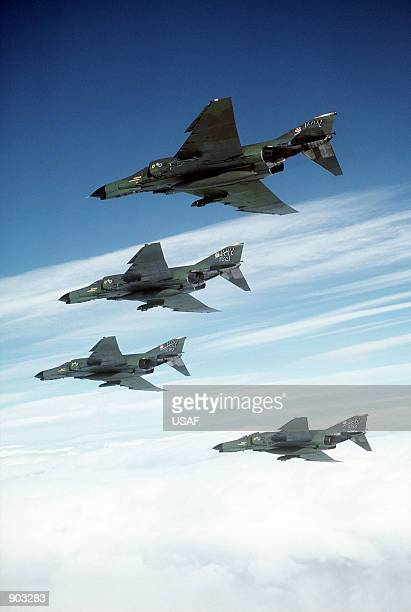 An airtoair left underside view of four 37th Tactical Fighter Wing F4E Phantom II aircraft in formation during the Tactical Air Command bombing and...