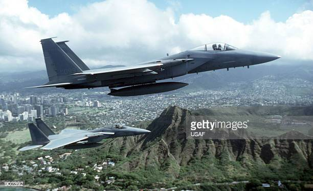 An airtoair right side view of two F15A Eagle aircraft from the 199th Tactical Fighter Squadron Hawaii Air National Guard over Diamond Head Crater