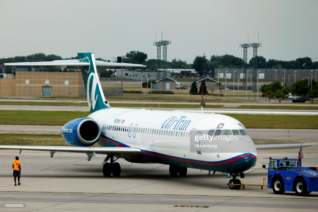 An AirTran Holdings Inc. Boeing 717-231 plane is guided to a gate at Minneapolis-St. Paul International Airport (MSP) in Minneapolis, Minnesota, U.S., on Sunday, Sept. 8, 2013. Yields on benchmark securities climbed to almost two-year highs as consumers spent more on travel and tourism while manufacturing expanded modestly from early July through late August, according to the Federal Reserves Beige Book. Photographer: Patrick T. Fallon/Bloomberg via Getty Images