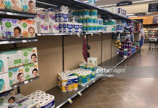 An aisle of toilet paper is nearly empty at a Kroger grocery store Shoppers have been panic buying toilet paper hand sanitizer paper towels cold and...