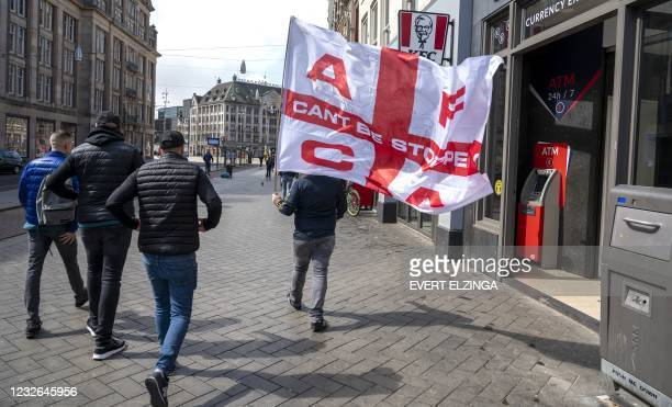An Ajax supporter carries a large flag of AFCA Supportersclub while walking into the city via the Damrak prior to the Dutch Eredivisie football match...