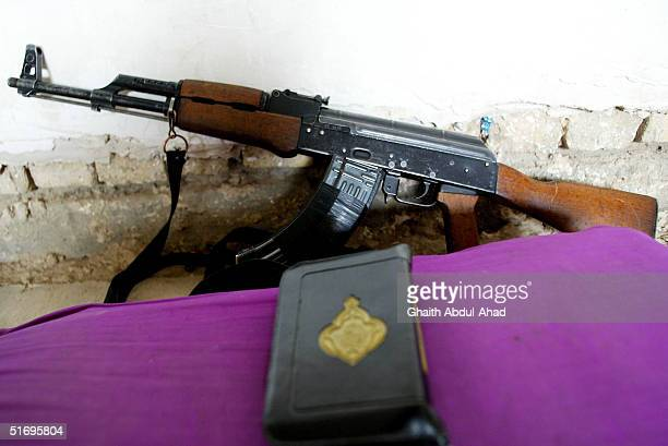 An AK47 rifle and a Quraan are pictured against a wall in a fighters nest on November 7 2004 in the city of Fallujah Iraq The Mujahadeen are...
