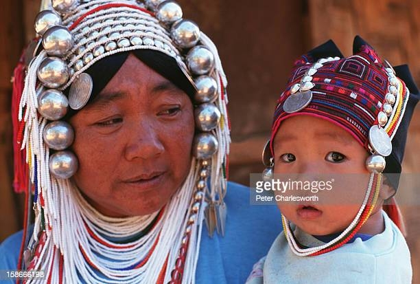 An Akha hill tribe woman wearing a traditional hill tribe costume including the elaborate head dress holds her son who also sports the traditional...