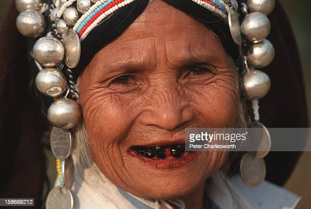 An Akha hill tribe woman wearing a traditional hill tribe headdress smiles Her teeth are discoloured from chewing beetlenut
