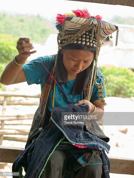 An Akha Nuquie woman sewing her traditional clothing in Ban Phanghok Phongsaly province Lao PDR One of the most ethnically diverse countries in...