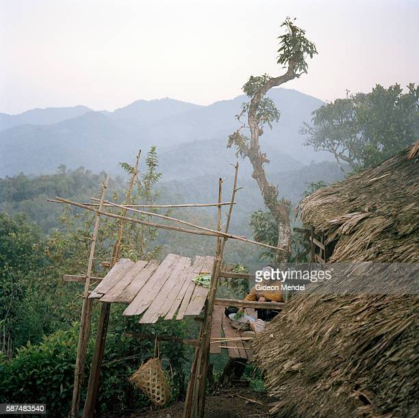 An Akha woman prepares the evening meal on the balcony of her traditional house in the Ban Nam Sa Akha village high up on a mountain slope in the Nam...
