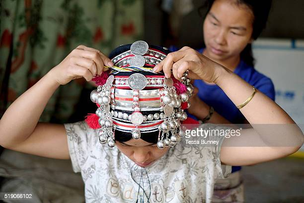 An Akha woman putting on her traditional headdress before a village wedding Ban Lang Pa Luang Namtha province Lao PDR Made from hand forged silver...