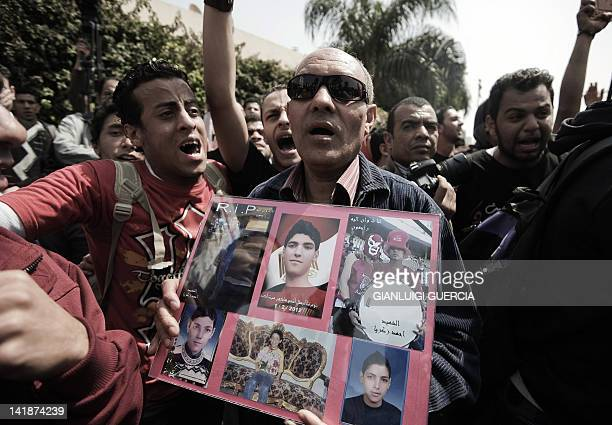 An al-Ahly supporter holds pictures of people killed during violence at the Port Said football stadium after an al-Ahly versus al-Masry football...