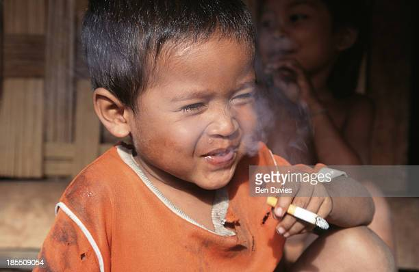 An Alak boy smokes a cigarrette in the village of Baan Kien Tang Le situated in a forest clearing near Tad Lo on the Bolovens Plateau in Southern...