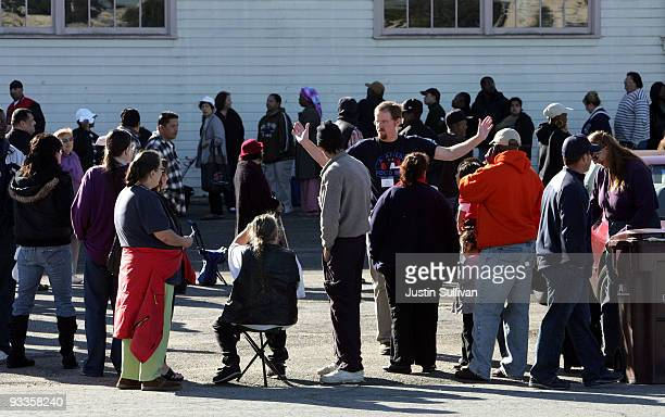 An Alameda Food Bank executive director Paul Russell talks with people lined up to receive a Thanksgiving turkey November 24 2009 at the Alameda Food...