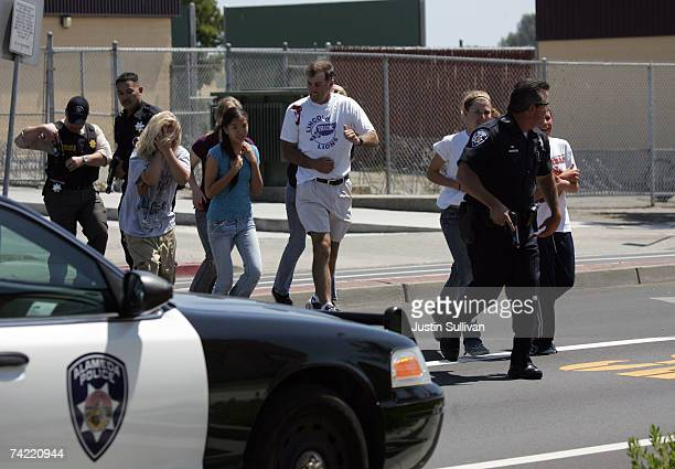 An Alameda Police officer evacuates volunteer students wearing makeup to simulate injuries during a school shooting and mass evacuation drill at...