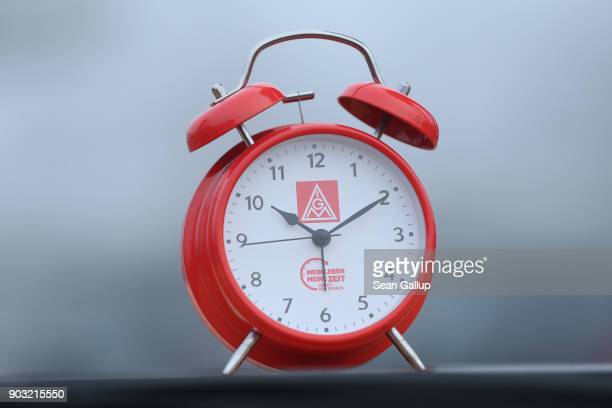 An alarm clock meant to symbolize the demand for workers to better determine their working hours stands near where workers from nearby Daimler and...