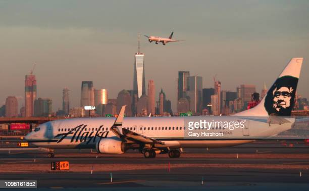 An Alaska Airlines airplane passes by the skyline of lower Manhattan in New York City as it heads to a gate at Newark Liberty Airport on January 21...