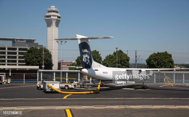 An Alaska Airlines Bombardier Q400 turbo prop jet plane is parked at the PDX terminal B on August 1 over Portland Oregon Portland is the largest city...