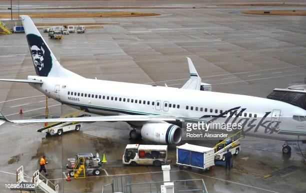 An Alaska Airlines passenger jet is serviced at a gate on a rainy day at Dallas/Fort Worth International Airport which serves the Dallas/Fort Worth...