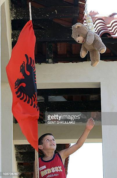 MEMA An Albanian boy looks up at a stuffed teddy bear and a string of garlic hung from a new building in Kuc near Tirana on July 29 2010 It is...