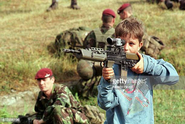 An Albanian child 'tries out' a UK paratrooper's SA 80 rifle.