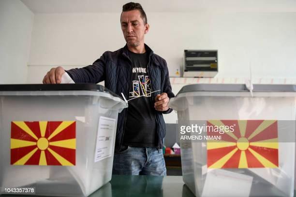 An Albanian man casts his vote at a polling station in the village of Zajas on September 30 for a referendum to rename the country Macedonians cast...