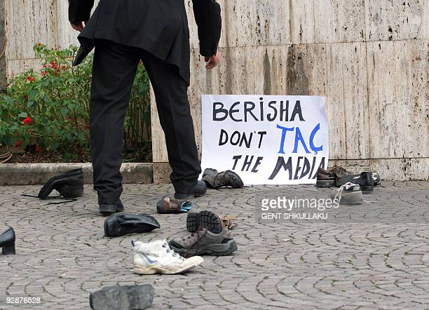 An Albanian policeman removes a banner after a protest of Albanian journalists in front of the government building in Tirana on November 4 2009 Mero...