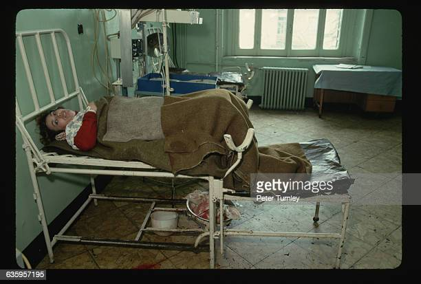 An Albanian woman lies on a rickety old delivery table on a spartan delivery room in Albania's capitol city