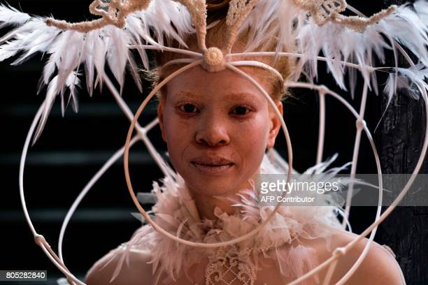TOPSHOT An albino model wearing a creation waits to access a private lounge during the fashion show at the 2017 Durban July horse race in Durban on...