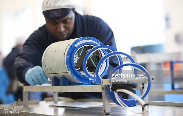 An AlcatelLucent employee inspects the internal parts of a repeater unit for a submerged fibre optic cable at AlcatelLucent's submarine networks...