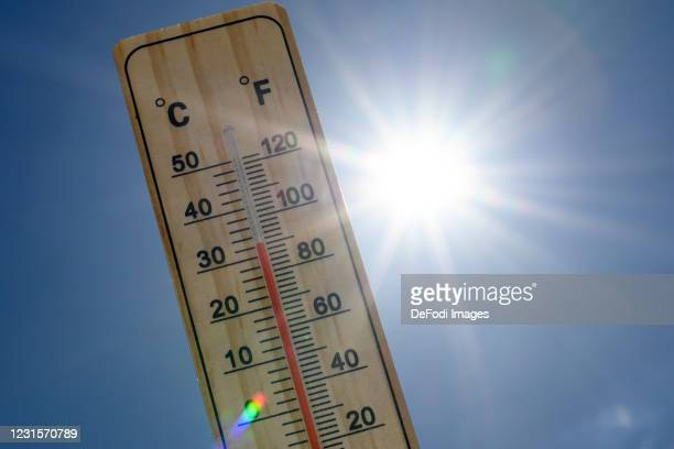 An alcohol thermometer is seen with the temperature 32 degrees Celsius or 90 degrees Fahrenheit in front of the radiant sun on May 29, 2020 in...
