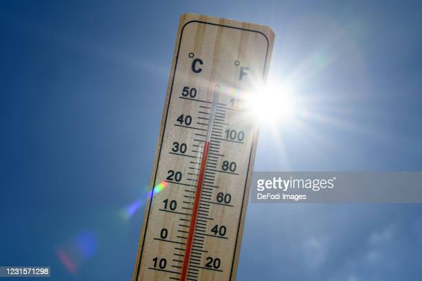 An alcohol thermometer is seen with the temperature 35 degrees Celsius or 95 degrees Fahrenheit in front of the radiant sun on May 29, 2020 in...