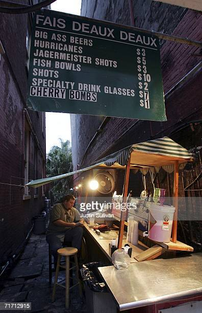 An alcohol vendor reads a book as he waits for customers along Bourbon Street August 24 2006 in the French Quarter of New Orleans Louisiana The...