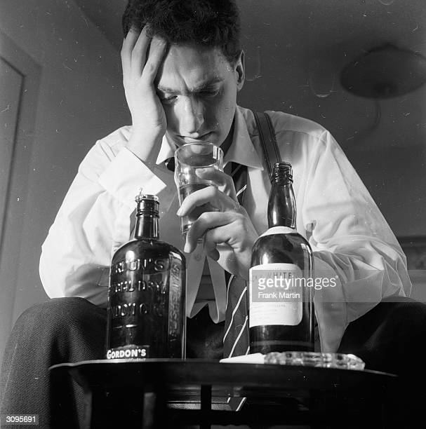 An alcoholic stares into the bottom of his glass while two bottles of spirits stand at the ready in front of him