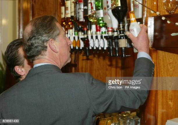An alcopop drink catches the eye of His Royal Highness Prince Charles in the Poet Laureate pub during his visit to the village of Poundbury in Dorset...