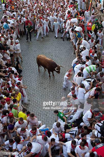 An Alcurrucen's ranch fighting bull stands alone surrounded by a crowd of runners on the way to entering the bullring during the second day of the...