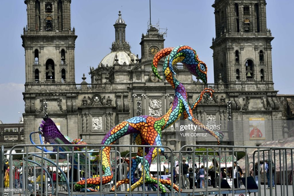 An alebrije - traditional Mexican folk art sculptures representing fantastical creatures - is on exhibit at the El Zocalo square during the 'In the heart of Mexico festival' in Mexico City on February 21, 2018. Representatives of all Mexican states present samples of their food, clothing and traditions during the festival. /