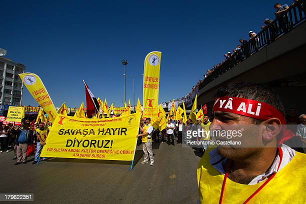 An Alevi protester watch the demonstration against government policy while others show banner opposing intervention in Syria's war.