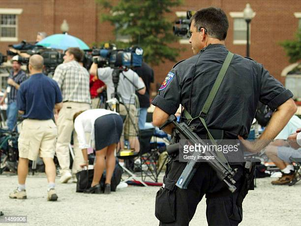 An Alexandria Police officer with a machine gun stands guard near the media who were covering American Taliban fighter John Walker Lindh's sentencing...
