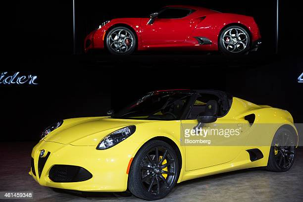 An Alfa Romeo 2015 4C Spider bottom and an Alfa Romeo 2015 4C Coupe both produced by Fiat Chrysler Automobiles NV sit on display during the 2015...