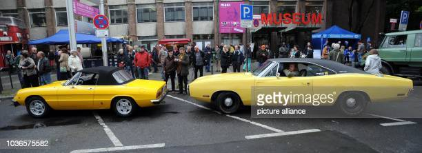 An Alfa Romeo Spider an a Dodge Charger go past the audience during the 'Drive it Day' in Cologne Germany 27 April 2014 Oldtimers are presented in...