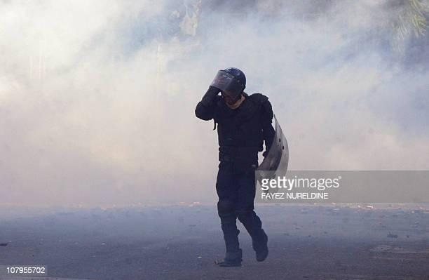 An Algerian antiriot policeman escapes from tear gaz during clashes linked to rising food costs and unemployment at Belcour distric of Algiers' city...