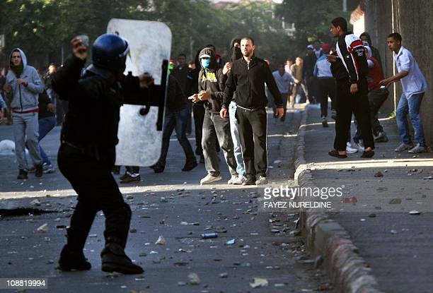 An Algerian antiriot policeman throws a stone at protesters during clashes linked to rising food costs and unemployment at Belcour distric of...