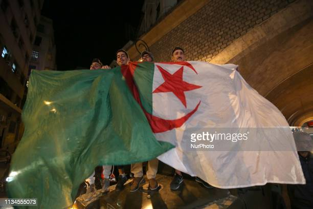 An Algerian brandishes his national flag while the people celebrates Algerian President Abdelaziz Bouteflika informed the Constitutional Council that...