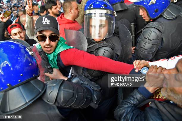 An Algerian demonstrator has his arm pulled between members of the security forces during a protest rally against ailing President Abdelaziz...