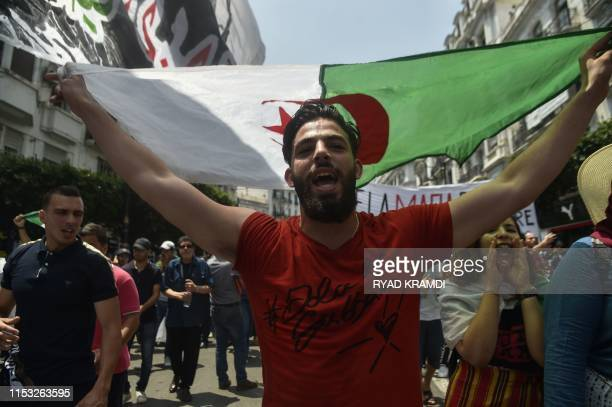 An Algerian demonstrator waves a national flag as he takes part in a protest in the capital Algiers on July 2 2019 Several hundred Algerian students...