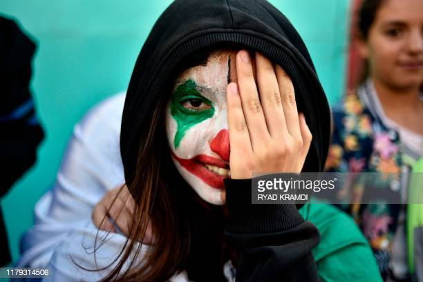 TOPSHOT An Algerian demonstrator wearing face paint of the DC comic book and film character 'Joker' takes part in an antigovernment demonstration in...