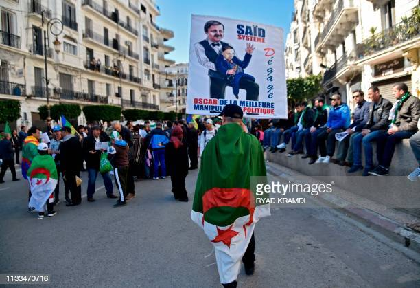 TOPSHOT An Algerian draped in the national flag take part in a demonstration against ailing President Abdelaziz Bouteflika in the capital Algiers on...