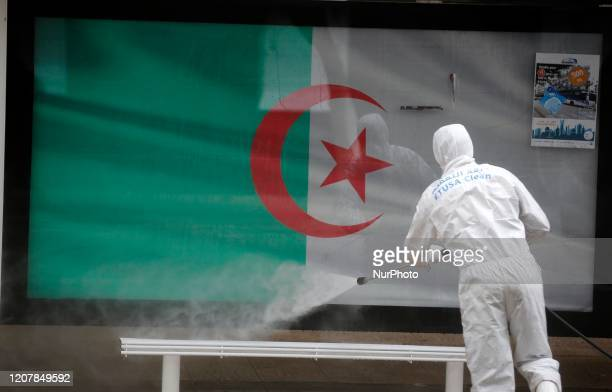 An Algerian health worker disinfects a bus stop in Algiers Algeria 20 March 2020 Friday prayers have been suspended in Algeria amid the spread of the...
